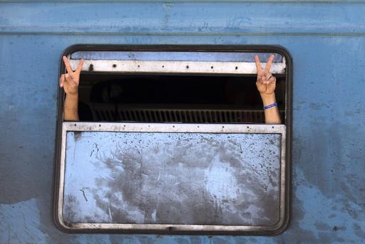 Migrants gesture after boarding a train after crossing the Macedonian-Greek border near Gevgelija