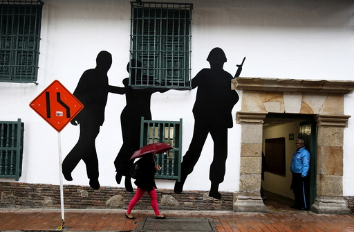 Citizens walk in front of a mural representing victims and missing people near the rebuilt Justice Palace in Bogota