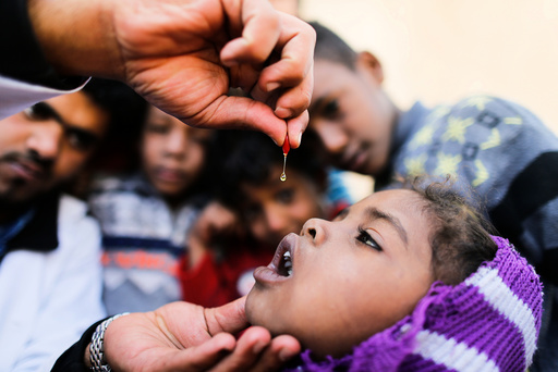 Girl is given vitamin A drops during a house-to-house vaccination campaign in Sanaa