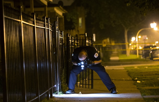 A Chicago police officer documents the crime scene where 7-year-old Amari Brown was shot and killed in Chicago
