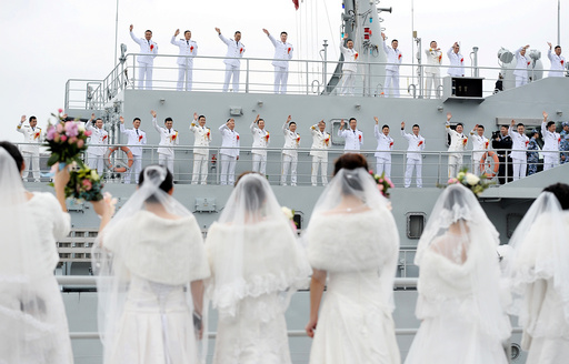 Navy personnel of People's Liberation Army (PLA) wave at their brides during a mass wedding at a military base in Zhoushan