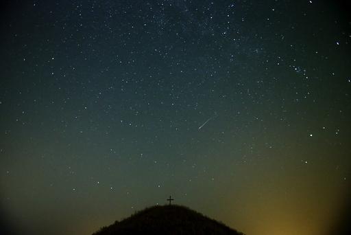 A meteor streaks across the sky over Leeberg hill during the Perseid meteor shower near Grossmugl