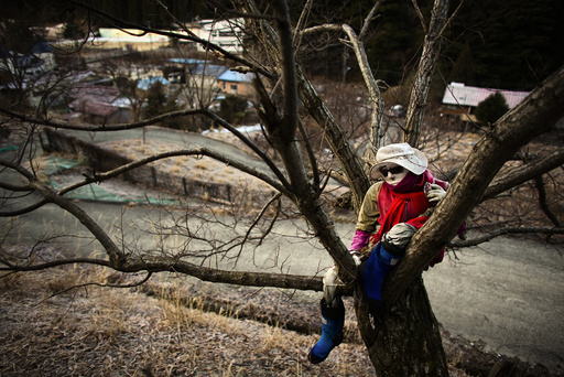 A scarecrow sits on a tree in the mountain village of Nagoro