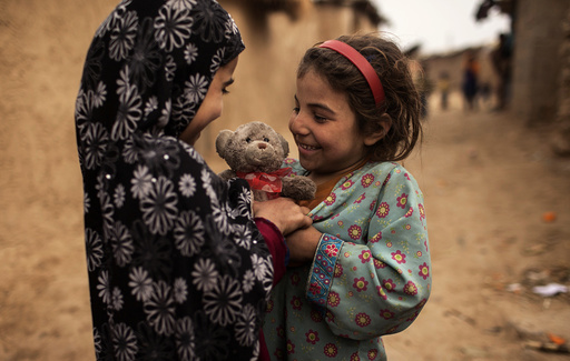 Afghan refugees smile as a girl presents a stuffed toy with a heart-shaped ribbon to her friend on Valentine's Day in a slum on the outskirts of Islamabad