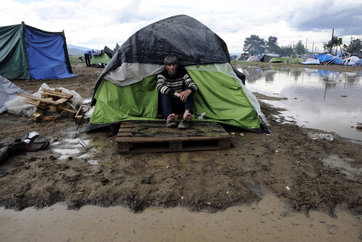 A refugee sits at the entrance of his tent following heavy rainfall at a makeshift camp for migrants and refugees at the Greek-Macedonian border near the village of Idomeni