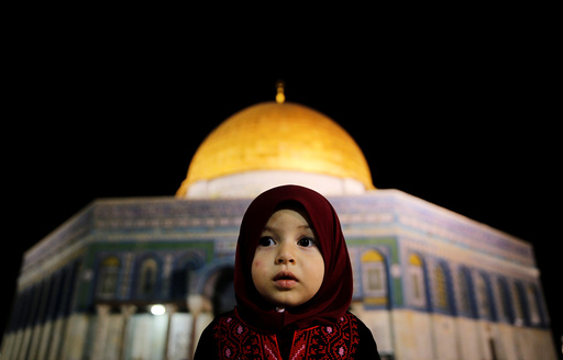 A Palestinian girl prays in front of the Dome of the Rock in Jerusalem's Old City during the holy month of Ramadan
