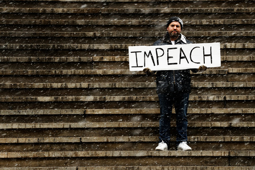 Ilan Bachrach holds a sign protesting the presidency of U.S. President Donald Trump on the steps of Federal Hall during a snow fall in New York,
