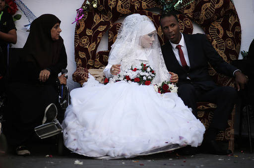 A Palestinian couple speaks with each other during their wedding ceremony at a United Nations-run school sheltering displaced Palestinians from the Israeli offensive, in Shati refugee camp in Gaza City