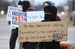 Demonstranter hadde møtt fram i Urbana i Illinois torsdag for å protestere mot henrettelsen av Corey Johnson. Christina Bollo holder et skilt som stiller spørsmål ved myndighetenes rett til å henrette folk. Foto: The Tribune-Star / AP / NTB