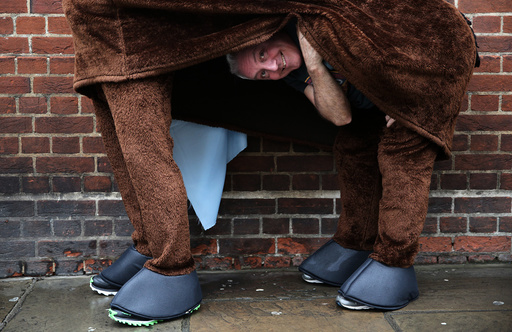 A participant peeks from his costume before the start of the the annual London Pantomime Horse Race in Greenwich, Britain