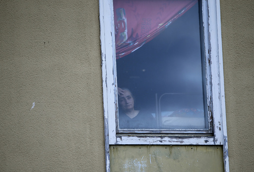 Woman looks out of window in refugee deportation registry centre in Manching