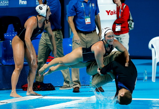 U.S. players push head coach Adam Krikorian into the pool after they defeated the Netherlands in their women's water polo gold medal match during the Aquatics World Championships in Kazan
