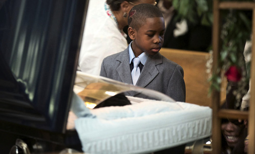 Ronnie Chambers Jr. looks at his mother Tahitah Myles as she collapses during the funeral for his father Ronnie Chambers, 33, a victim of gun violence, in Chicago