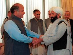 Mohammad Hassan Akhund (til høyre) i 1999, da han var utenriksminister i Afghanistan. Her tas han imot av Pakistans daværende statsminister Nawaz Sharif i Islamabad. Foto: B.K. Bangash / AP / NTB