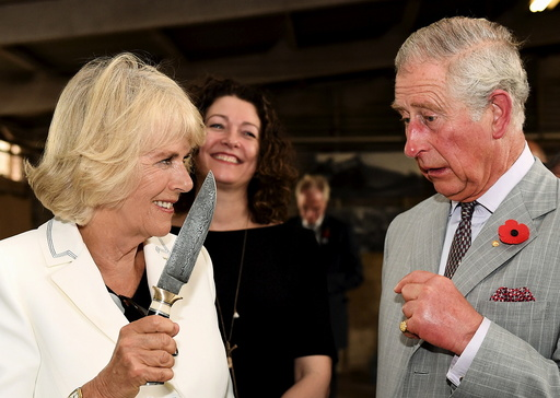 Britain's Prince Charles watches on as Camilla, Duchess of Cornwall holds a knife as they visit Seppeltsfield Winery in South Australia's Barossa Valley