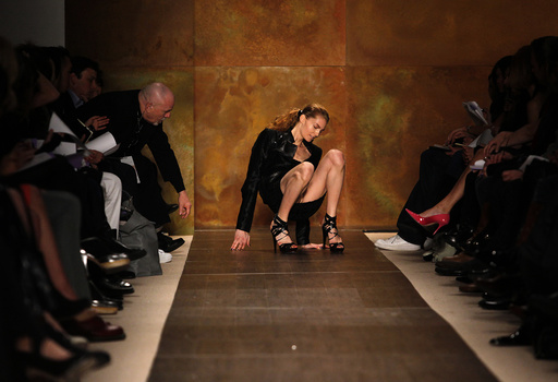 A model slips and falls while presenting a creation from the Herve Leger by Max Azria Fall 2009 collection during New York Fashion Week