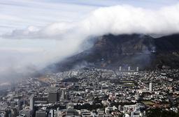 Røykskyene legger seg over Cape Town mens brannen herjer ved byens kjennemerke Table Mountain. Foto: Nardus Engelbrecht / AP / NTB