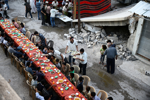 People gather for Iftar amidst damaged buildings during the holy month of Ramadan in the rebel held besieged Douma neighbourhood