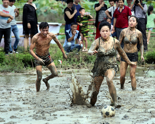 People fight for the ball as they take part in a mud football match in Jinhua