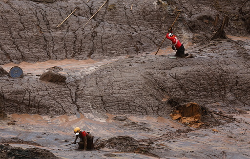 Rescue workers search for victims at the Bento Rodrigues district that was covered with mud after a dam, owned by Vale SA and BHP Billiton Ltd, burst in Mariana