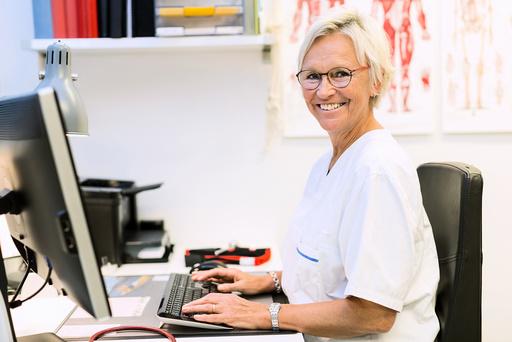 Portrait of happy senior orthopedic surgeon using computer at desk in clinic