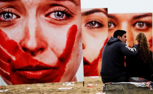 Activists talk in front photos from Brazilian photographer Marcio Freitas, during a protest by NGO Rio de Paz against rape and violence against women on Copacabana beach in Rio de Janeiro