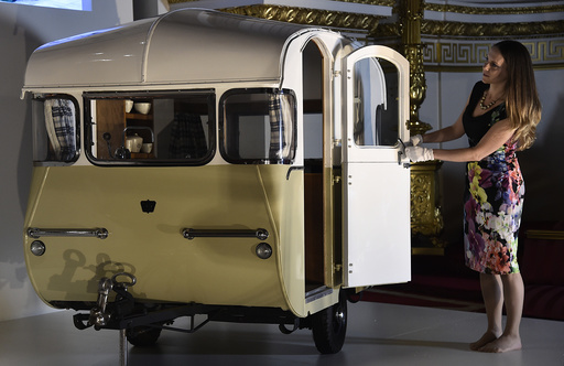 Curator of Royal Collection Trust Reynolds poses with a miniature caravan at Buckingham Palace in central London