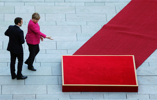 FILE PHOTO: German Chancellor Angela Merkel and French President Emmanuel Macron arrive at a ceremony at the Chancellery in Berlin