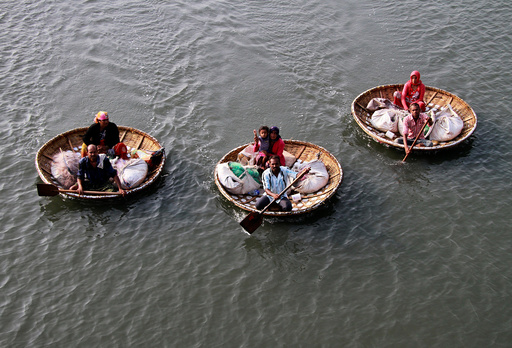 Fishermen paddle their boats as they carry their family members in the waters of Vembanad Lake in Kochi