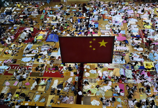 Students prepare to sleep on mats laid out on the floor under a Chinese national flag inside a gymnasium at the Huazhong Normal University in Wuhan, China