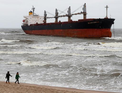 People walk past stranded cargo ship Ocean Crown in Klaipeda