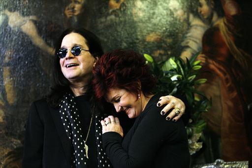 Ozzy and Sharon Osbourne smile pose in front of their belongings in Beverly Hills