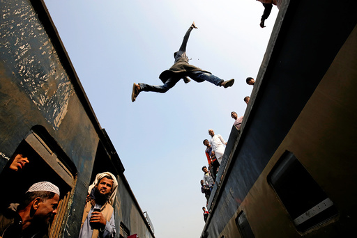 A commuter jumps between trains upon arrival at a station on the outskirts of Dhaka