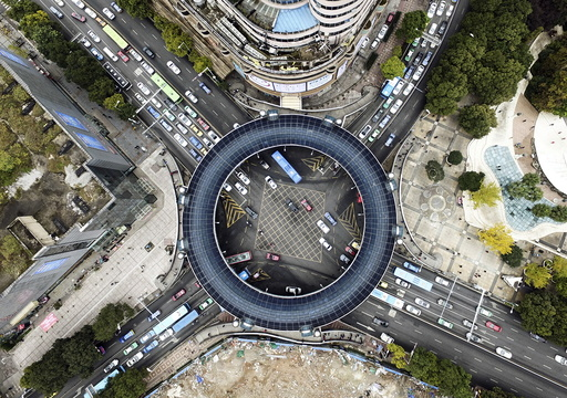 An aerial view shows cars passing below a pedestrian overpass in the shape of a circle in Guiyang