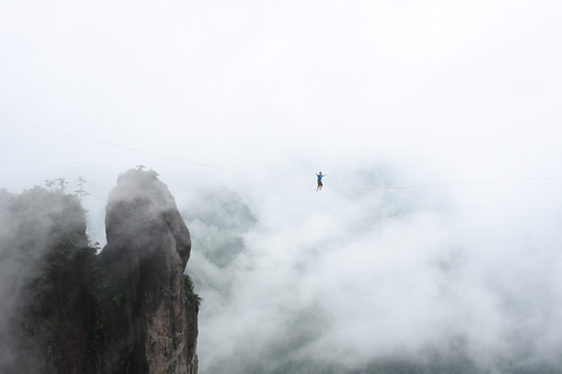 A competitor walks on tightrope during a performance in Taizhou