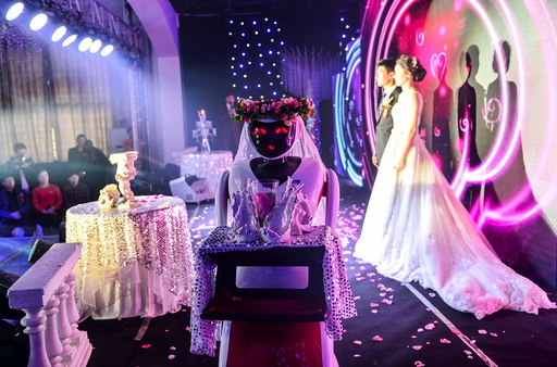A robot dressed up as a bridesmaid carries glasses as it serves a wedding in Tianjin
