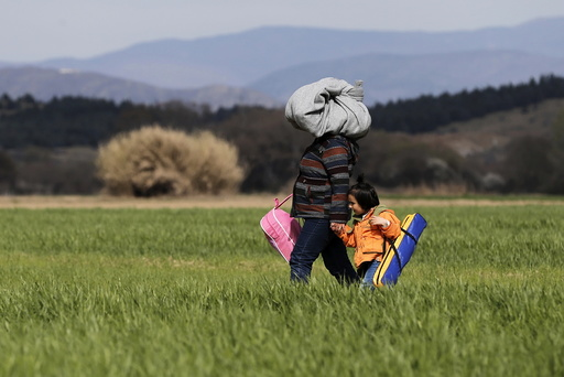 A migrant walks with a child through a field towards a makeshift camp at the Greek-Macedonian border, near the village of Idomeni