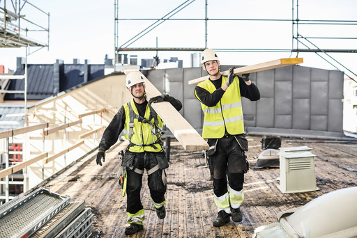 Construction workers carrying wooden planks at site