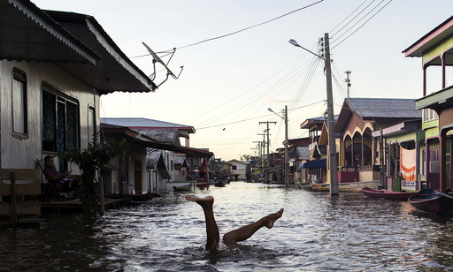 A child jokes in a street flooded by the rising Rio Solimoes, one of the two main branches of the Amazon River, in Anama