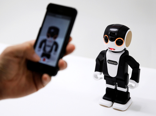 A visitor records a videoclip of Sharp Corp's RoBoHon, a humanoid communication robot shaped mobile phone, during its unveiling event in Tokyo