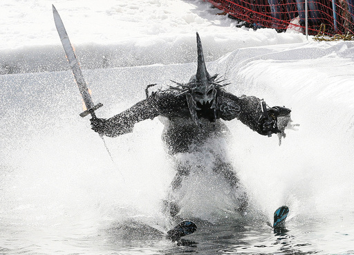 Skier in costume attempts to cross pool of water at foot of ski slope while competing in annual