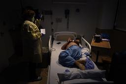 En sykehusprest ber med en pasient ved et sykehus i Los Angeles. Sykehus i flere deler av de amerikanske kontinentene er sterkt presset av koronapandemien. Foto: Jae C. Hong / AP / NTB