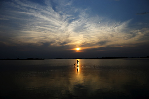 A boy is silhouetted as he paddles on a stand up board on Lake Zicksee in St. Andrae