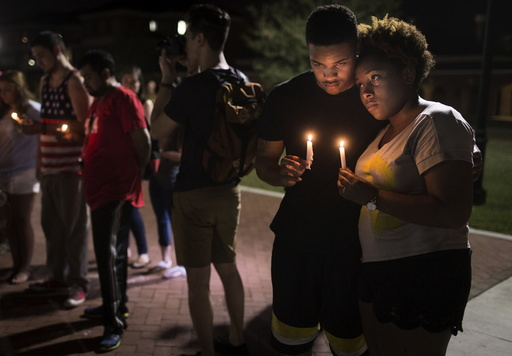 Sheldon Gilton and Brea Butler hold candles during a candlelight vigil for victims of the Thursday night shooting at a movie theater in Lafayette