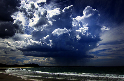 A giant storm cloud can be seen in the sky above swimmers near Mollymook Beach, south of Sydney