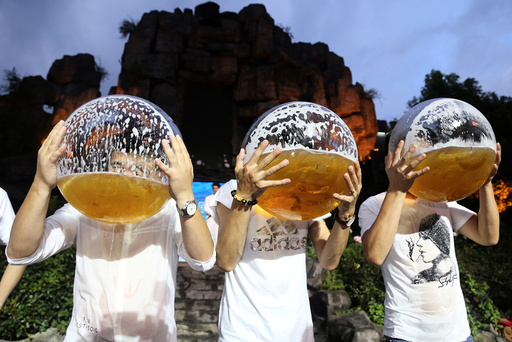 People drink beer from fish bowls at a beer drinking competition in Hangzhou
