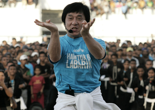 Action film star and UNICEF Goodwill Ambassador Chan demonstrates martial arts move in front of East Timorese youths in Dili