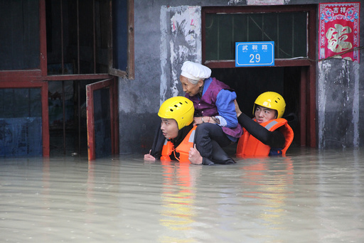 Rescuers save a resident from a flooded building in Chongqing