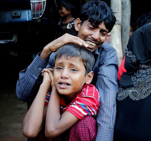 A Rohingya Muslim man and his son cry after being caught by Border Guard Bangladesh while illegally crossing at a border check point in Cox's Bazar