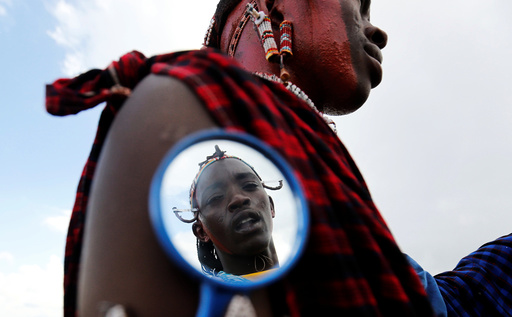 A Maasai moran athlete is reflected in a grooming mirror as he smears his colleague's face with red ocher paint during preparations for the 2016 Maasai Olympics at the Sidai Oleng Wildlife Sanctuary, at the base of Mt. Kilimanjaro, in Kimana